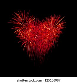 Flame fireworks in heart shape on the black sky background