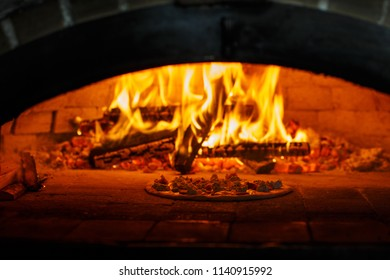 Flame in the furnace. Aromatic pizza in the baking process