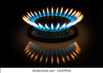 Flame of gas burner forming crown form in dark.