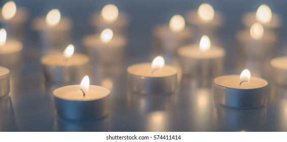 Flame of many candles burning on the background in blue and yellow color