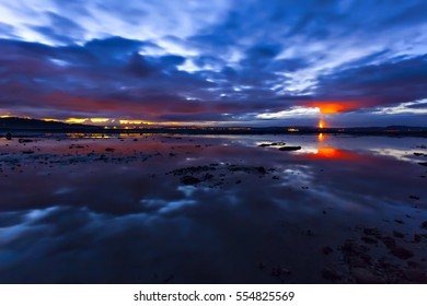 Flame on horizon of night cloudscape scene over water surface. Edinburgh, Scotland.