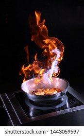 Flame over the pan when cooking flambe fruit. Food show at restaurant visitors. The concept of high cuisine.