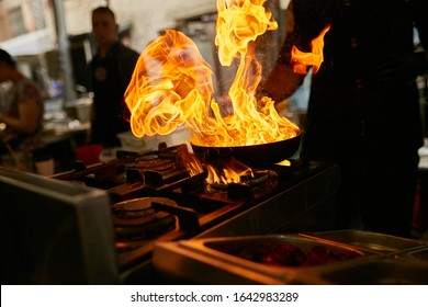 flame in the pan. Professional Chef makes flambe for food in the restaurant kitchen. Chef cooking with open fire pan.  on a stove. Fire burn is cooking on iron pan,stir fire very hot