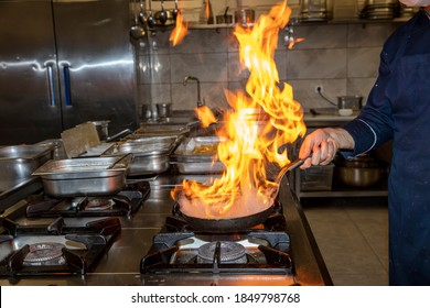Flame in the pan. Professional Chef makes flambe for food in the restaurant kitchen. Chef cooking with open fire pan on a stove.