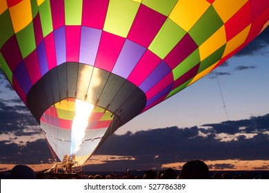 A flame reaches high into an inflating balloon envelope at sunrise Dawn Patrol during the Albuquerque International Balloon Fiesta