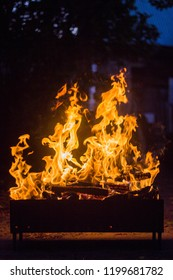 Flame rising from burning charcoal and wood in a mangal.