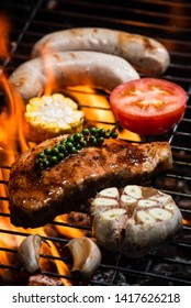 Flame roasted sirloin pork steak with garlic, sweet corn, tomatoes and sausage grilled on barbecue