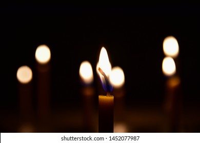 The flame of the yellow candle in the dark room. The background is a bokeh from the candlelight.