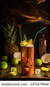 Flamed Tiki pineapple exotic cocktail, umber mug on a dark background. Bar fire show.