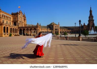 Flamenco dancer dancing with spanish shawl on Plaza de Espana in Seville, Spain