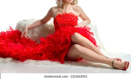 Flamenco dancer girl dressed in a red  resting before the performance. Red dress with ruffles and frills used to wear as a costume for performing flamenco dancing. Body part cropped, woman body part.