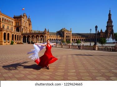 Flamenco dancer in red dress and white spanish shawl dancing on Plaza de Espana during Feria de Abril (april fair) in Seville, Spain