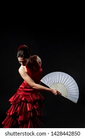 Flamenco dancer in a red lush dress with a white fan on a black background.