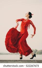 Flamenco dancer Spain womans in a long red dress dancing outside