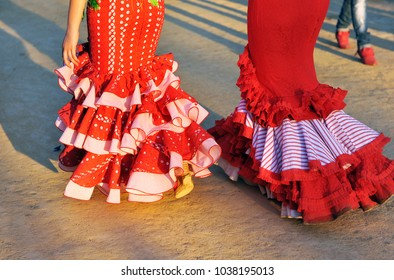 Flamenco fashion full of color, two Andalusian women in traditional costumes (gypsy costumes) walking in style at the Feria de Abril, Feria de Sevilla, Andalucía, Spain