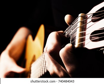 Flamenco guitar player close up, playing traditional acoustic guitar concept image us as background, high contrast, selective focus on foreground fingers