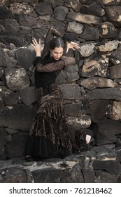flamenco in low-key, young attractive woman dances flamenco on volcanic stone steps