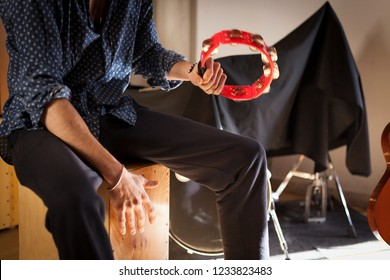Flamenco percussion player sitting on a drum box and playing while holds and plays a red tambourine with his other hand on a studio with instruments on the background.