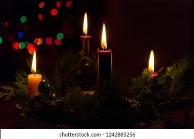 The flames of Advent candles joyously rise above their wreath