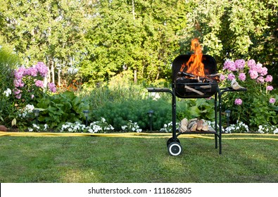 Flames burning in a barbecue standing in a pretty garden as the coals are prepared for grilling an array of meat for a lunchtime cookout