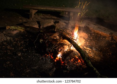 Flames of a cozy campfire flicker in a light breeze