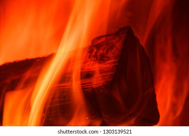 Flames crawl up the side of a single log. Close-up photo of fire in a stove