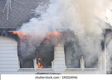 Flames are evident through the windows of a burning house during a training fire
