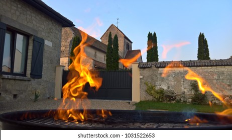 Flames licking across the foreground with an old church behind