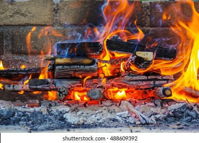 a flames on a Barbecue grill with lot of charcoal