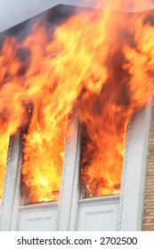 Flames shooting out of the windows of a burning apartment