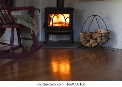 Flames in small wood burning stove reflecting on wooden parquet floor, firewood and rocking chair with plaide in dim living room in Scandinavia