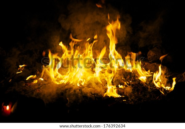 Flames and smoke fill this image of a ceremonial fire during a mayan ritual.