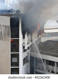 flames and smoke rise from burning building