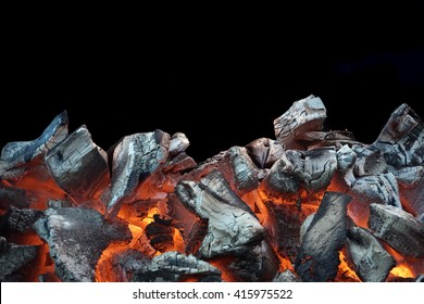 Flaming Charcoal In BBQ Grill Pit Isolated On Black Background