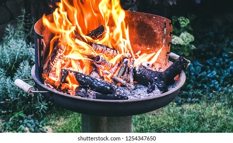 Flaming grill with open fire, ready for product placement. Summer or autumn charcoal, wood grilling, barbecue, bbq and party. Empty device for cook food as meat, seafood, chicken apply heat from below