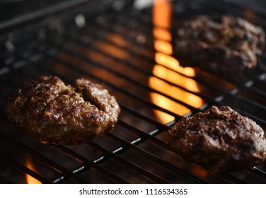 Flaming hot beer burgers on grill. Delicious fresh food close up.