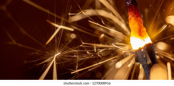 Flaming sparkler on red background close up macro