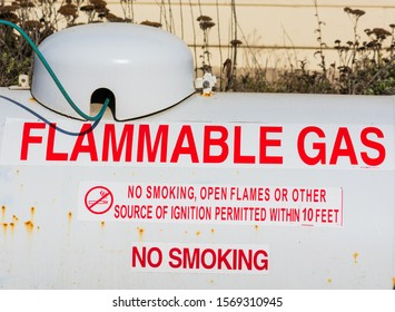 Flammable gas warning on above ground large propane tank. Rust or corrosion on the white propane tank surface.