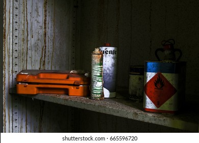 flammable liquid and an orange tools case in a rusty metal locker in am abandoned psychiatric hospital