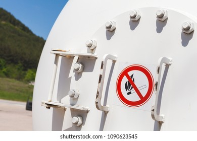 Flammable warning sign on white tank with liquefied petroleum gas stands on a gas station