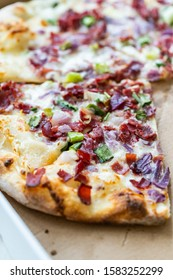 Flammkuchen Pizza Slices / Traditional Tarte Flambee with Creme Fraiche, Cream Cheese, Bacon and Red Onions in Box.