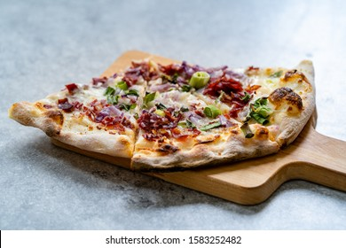 Flammkuchen Pizza Slices / Traditional Tarte Flambee with Creme Fraiche, Cream Cheese, Bacon and Red Onions on Wooden Board.