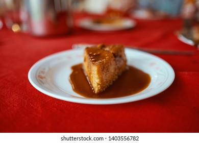 Flan, Traditional dessert called quesillo, made with eggs and sugar, seem from a side over a table cover with a red tablecloth dip in sugar cane caramel