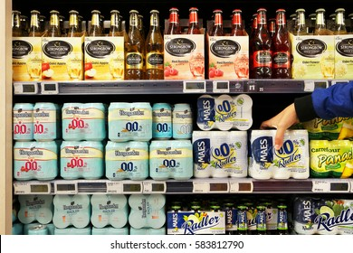 FLANDERS, BELGIUM - OCTOBER 20, 2016: Aisle with assortment Hoegaarden 0.0 beers and Strongbow apple ciders in a Carrefour Hypermarket. Strongbow is the world's leading cider produced by H. P. Bulmer.