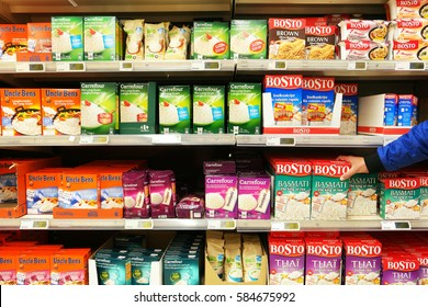 FLANDERS, BELGIUM - OCTOBER 20, 2016: Aisle with various brands and different types of rice packaging in a Carrefour Hypermarket. Rice is the most widely consumed staple food for the human population.