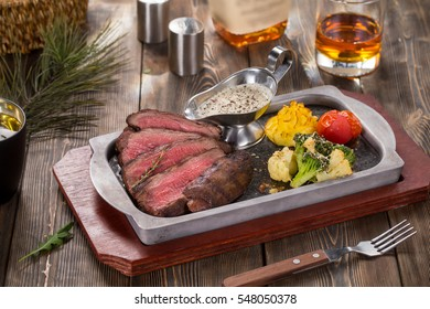 Flank steak with bbq vegetables in pan on wooded rustic background with bottle and glass of whiskey in soft focus.