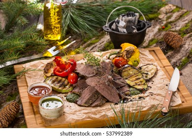 Flank steak on paper and dark wood table with bark