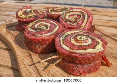 Flank steak rolls stuffed with cheese and pesto on a wooden board on a wooden table outside
