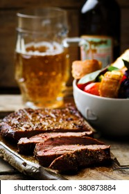 flank steak  with tomato salad and glass of beer. style vintage.  selective focus