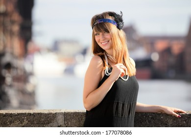 Flapper girl. Retro styled fashion portrait of vintage woman from roaring 1920s outdoor. Old town Gdansk in the background